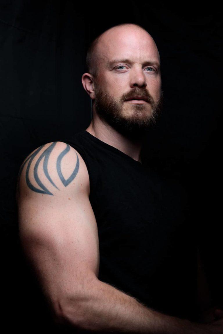 Portraitbild-Mann-schwarz-muskulös-schaut-nach-unten-zum-fotograf