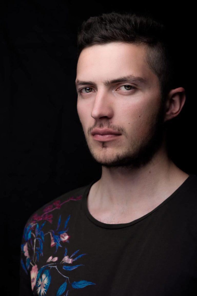 Portraitbild-Mann-schwarz-schaut-schräg-zum-fotograf