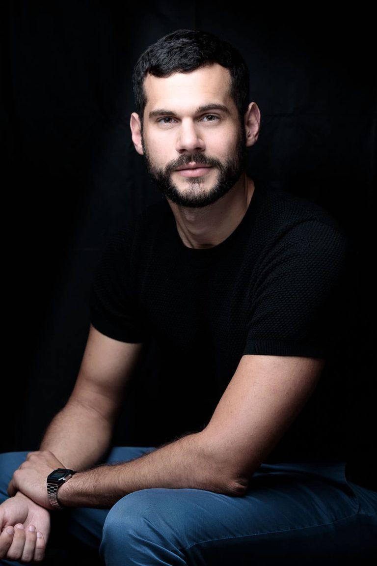 Portraitbild-Mann-schwarz-sitzend-schaut-zum-fotograf