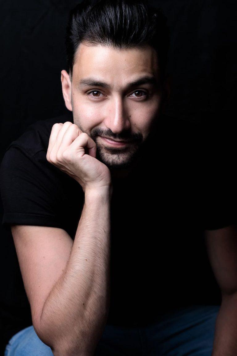 Portraitbild-Mann-schwarz-stützt_sein-gesicht-mit-derhand-ab