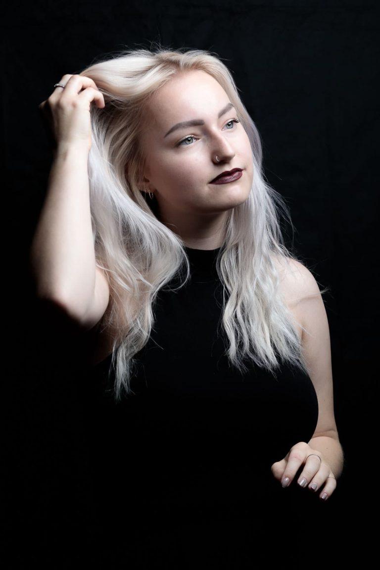 Portraitbild-frau-schwarz-geht-mit-der-hand-durch-die-haare